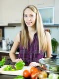 Счастливая девушка варя с овощами Стоковая Фотография