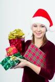 Счастливая девушка в шляпе santa с подарочными коробками Стоковая Фотография RF