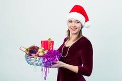 Счастливая девушка в шляпе santa с подарочными коробками Стоковые Фотографии RF
