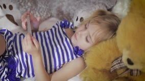Счастливая девушка лежа в кровати с smartphone дома видеоматериал