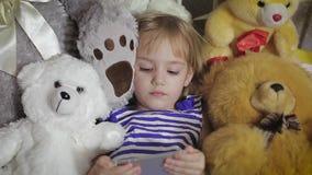 Счастливая девушка лежа в кровати с smartphone дома акции видеоматериалы