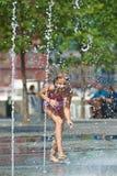 Счастливая девушка играя в фонтане Стоковые Изображения