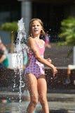 Счастливая девушка играя в фонтане Стоковое Фото