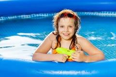 Счастливая девушка играя с водяным пистолетом в бассейне Стоковые Фотографии RF