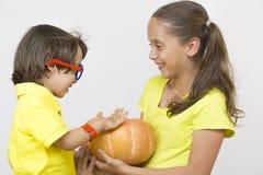 Счастливая девушка и мальчик держа тыкву Стоковые Изображения RF