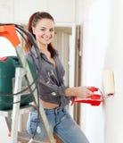 Счастливая девушка красит стену с роликом дома Стоковое фото RF