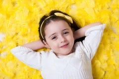 Счастливая девушка кладя на желтое перо Стоковые Фото