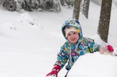 Счастливая девушка малыша в теплом пальто и связанной шляпе меча вверх по снегу и имея потеху в зиме снаружи, внешний портрет Стоковое фото RF