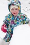 Счастливая девушка малыша в теплом пальто и связанной шляпе меча вверх по снегу и имея потеху в зиме снаружи, внешний портрет Стоковые Фото