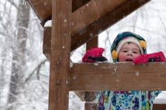 Счастливая девушка малыша в теплом пальто и связанной шляпе меча вверх по снегу и имея потеху в зиме снаружи, внешний портрет Стоковая Фотография RF