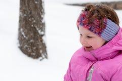 Счастливая девушка малыша в теплом пальто и связанной шляпе меча вверх по снегу и имея потеху в зиме снаружи, внешний портрет Стоковое Изображение