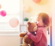 Счастливая девушка малыша играя с ее плюшевым медвежонком стоковая фотография rf