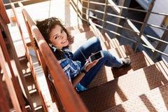 Счастливая девушка мулата используя мобильный телефон на лестницах Стоковая Фотография