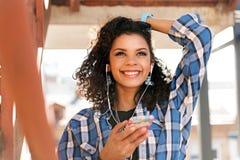 Счастливая девушка мулата используя мобильный телефон снаружи Стоковое Изображение