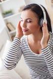 Счастливая девушка наслаждаясь мелодией от наушников стоковое фото rf