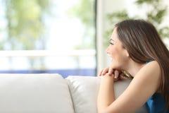 Счастливая девушка на кресле смотря через окно Стоковая Фотография