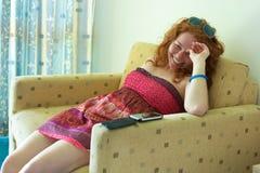 Счастливая девушка на софе Стоковая Фотография RF