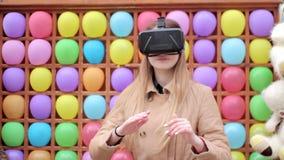 Счастливая девушка на улице в бежевом пальто играя имеющ стекла шлемофона виртуальной реальности vr потехи нося, красочную предпо акции видеоматериалы