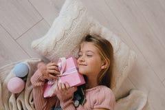 Счастливая девушка обнимая подарочную коробку рождества Оягнитесь лежать на подушке и держать настоящий момент Стоковое Изображение