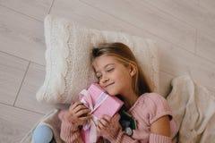 Счастливая девушка обнимая подарочную коробку рождества Оягнитесь лежать на подушке и держать настоящий момент Стоковые Фото