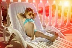 Счастливая девушка ослабляет в lounger солнца на заходе солнца Стоковые Фотографии RF