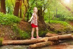 Счастливая девушка пересекая реку в лесе Стоковое Изображение RF
