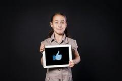 Счастливая девушка показывает экран таблетки с большим пальцем руки вверх по значку Стоковое Изображение RF