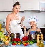 Счастливая девушка помогая ее матери подготавливает Стоковые Фотографии RF
