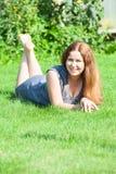 Счастливая девушка при красные волосы лежа на траве и усмехаться Стоковая Фотография RF