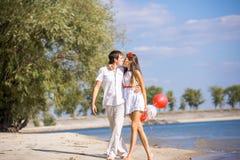 Счастливая девушка при парень сидя на пляже весной, лето Стоковые Изображения RF