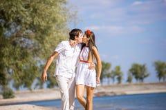 Счастливая девушка при парень сидя на пляже весной, лето Стоковое Изображение
