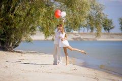 Счастливая девушка при парень сидя на пляже весной, лето Стоковые Изображения