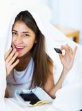 Счастливая девушка пряча под листом с помадками внутри помещения Стоковое Фото