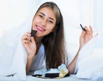Счастливая девушка пряча под листом с помадками внутри помещения Стоковое Изображение