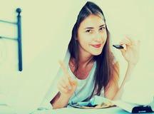 Счастливая девушка пряча под листом с помадками внутри помещения Стоковая Фотография RF