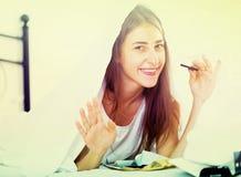 Счастливая девушка пряча под листом с помадками внутри помещения Стоковые Изображения RF