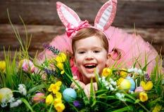 Счастливая девушка ребенка в костюме зайчика пасхи с яичками Стоковые Изображения