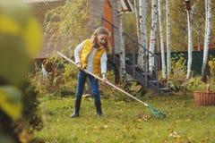Счастливая девушка ребенка играя маленький садовника в осени и выбирая выходит в корзину Сезонная работа сада стоковая фотография