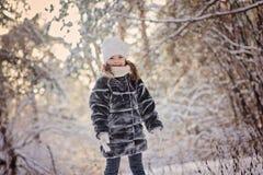 Счастливая девушка ребенка имея потеху в лесе зимы снежном Стоковые Фотографии RF