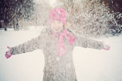Счастливая девушка ребенка имея потеху играя с снегом Стоковые Изображения RF