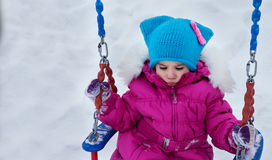 Счастливая девушка ребенка на качании в зиме захода солнца Маленький ребенок играя на прогулке зимы в природе Стоковые Фото