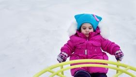 Счастливая девушка ребенка на качании в зиме захода солнца Маленький ребенок играя на прогулке зимы в природе Стоковая Фотография