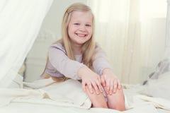Счастливая девушка ребенка сидит в белой кровати Стоковые Изображения RF