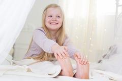 Счастливая девушка ребенка сидит в кровати, добром утре Стоковые Фото