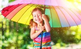Счастливая девушка ребенка смеется над и играется под дождем лета с umbr Стоковое Изображение