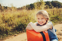 Счастливая девушка ребенка с оранжевым чемоданом путешествуя самостоятельно на летних каникулах Ребенк идя к летнего лагеря Стоковые Фото