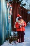 Счастливая девушка ребенка с украшениями рождества на деревянном обнести зима, уютные праздники стиля страны стоковое изображение rf