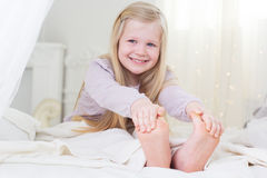 Счастливая девушка ребенка усмехается в кровати barefoot Стоковые Изображения RF
