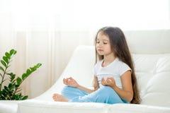 Счастливая девушка ребенк делая йогу дома Стоковая Фотография