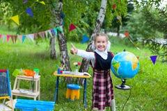 Счастливая девушка ребенк ребенка школьницы держа глобус и усмехаясь, большой палец руки Стоковое Изображение RF